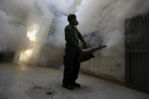 A municipal worker fumigates inside a building to help control the spread of the mosquito-borne Zika virus in Caracas